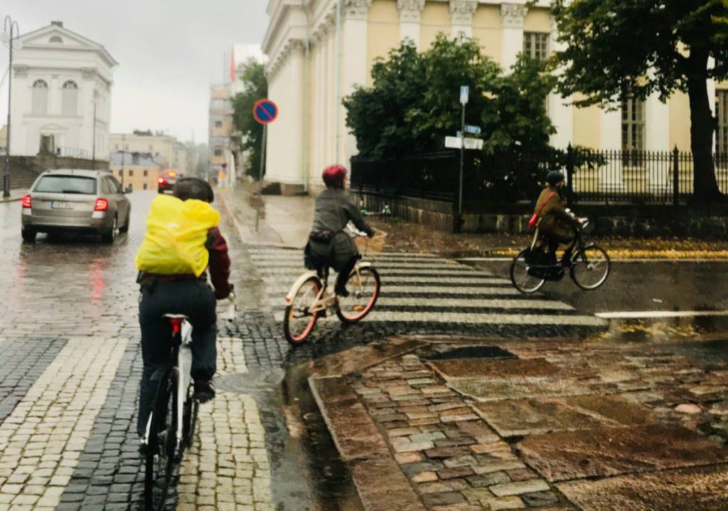 kolme pyöräilijää ja auto Helsingin kaduilla